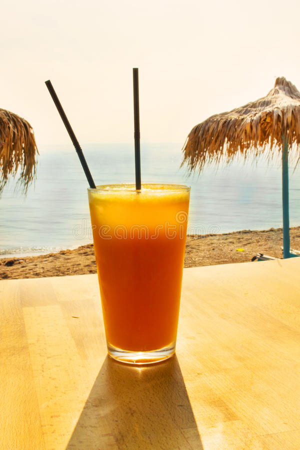 Fresh orange juice on the beach. Close up of an orange juice on a table at the beach with straw umbrellas stock photography