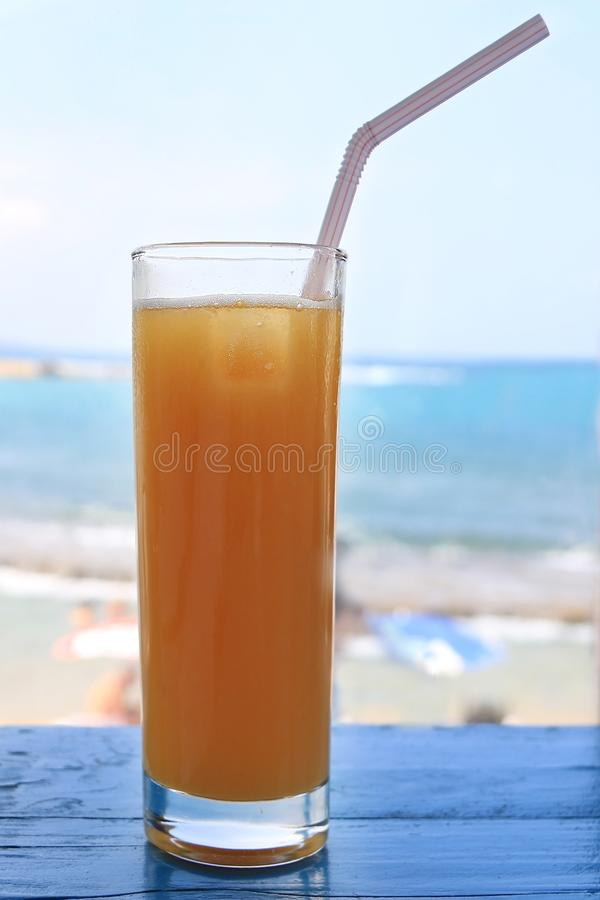 Fresh Orange Juice on Beach. A glass of fresh orange juice on a blue wooden table with the beach and Mediterranean sea in the background royalty free stock image