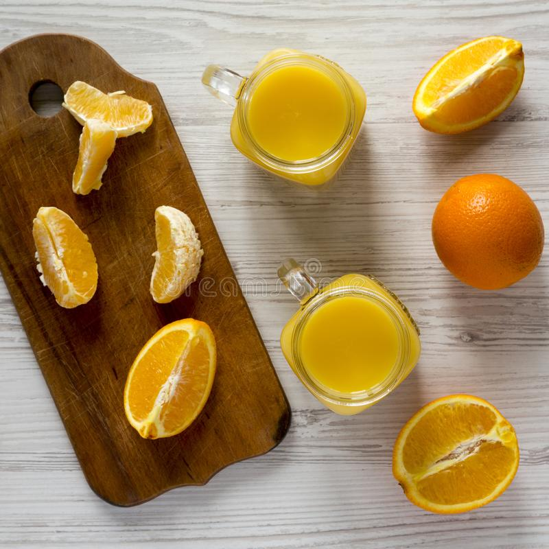 Fresh orange juice in glass jars over white wooden backgroun, top view. Flat lay, from above, overhead. Fresh orange juice in glass jars over white wooden royalty free stock photo