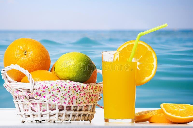 Fresh orange juice, orange slices and oranges in basket against background of surface blue sea. Summer tropical citrus fruits stock photo