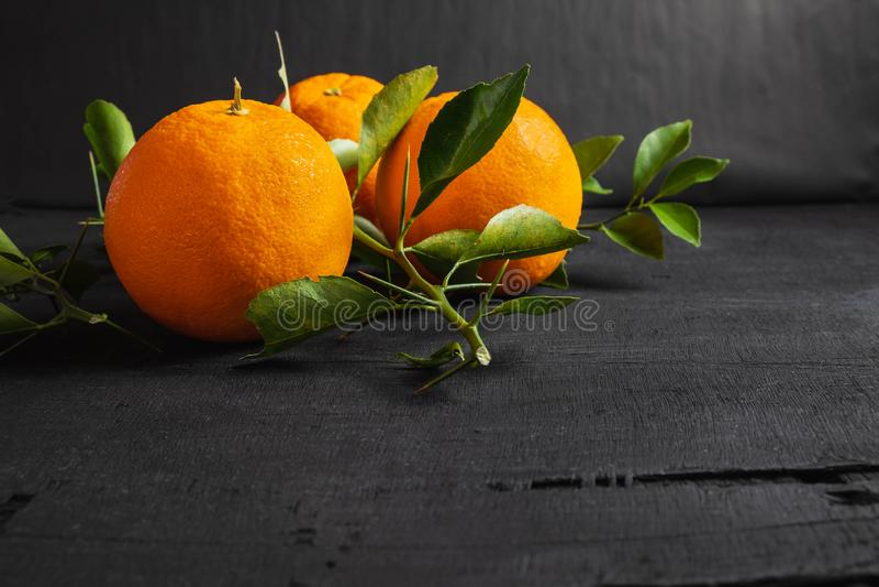 Fresh orange and leaf on black background. Fresh orange and leaf on wood royalty free stock photography