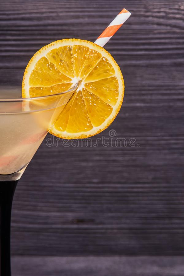 Fresh orange martini. Orange slice on the edge of the martini glass and a cocktail tube, on a dark wooden background. Close-up royalty free stock image