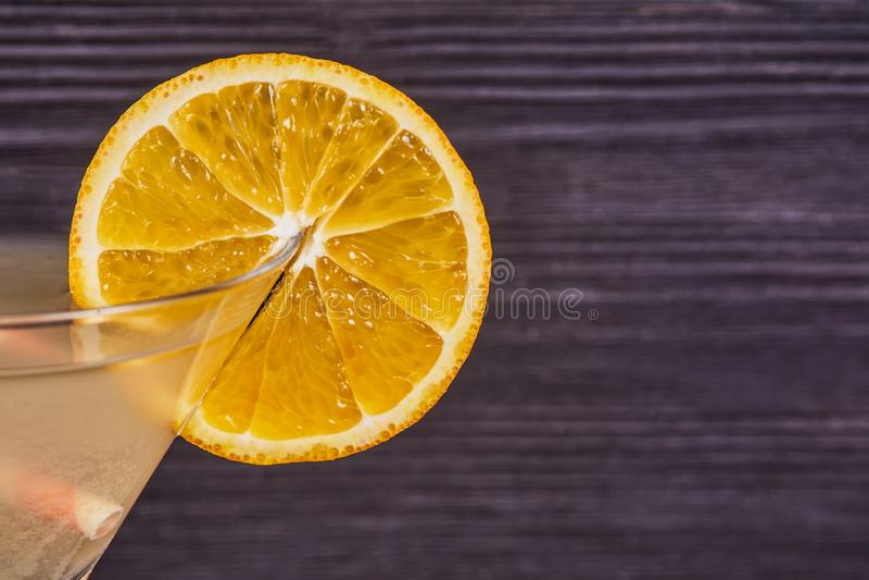 Fresh orange martini. Orange slice on the edge of the martini glass, on a dark wooden background. Close-up royalty free stock photography