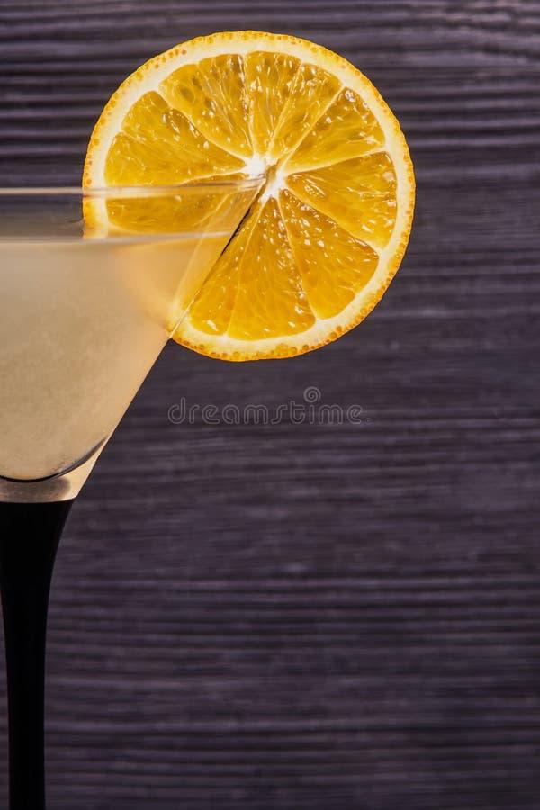 Fresh orange martini. Orange slice on the edge of the martini glass, on a dark wooden background. Close-up stock image