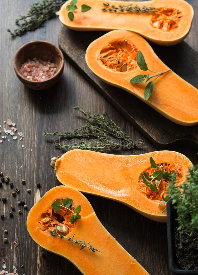 Fresh orange muscat pumpkin, cut in half, ready for baking with spices and herbs on wood board and table. royalty free stock image
