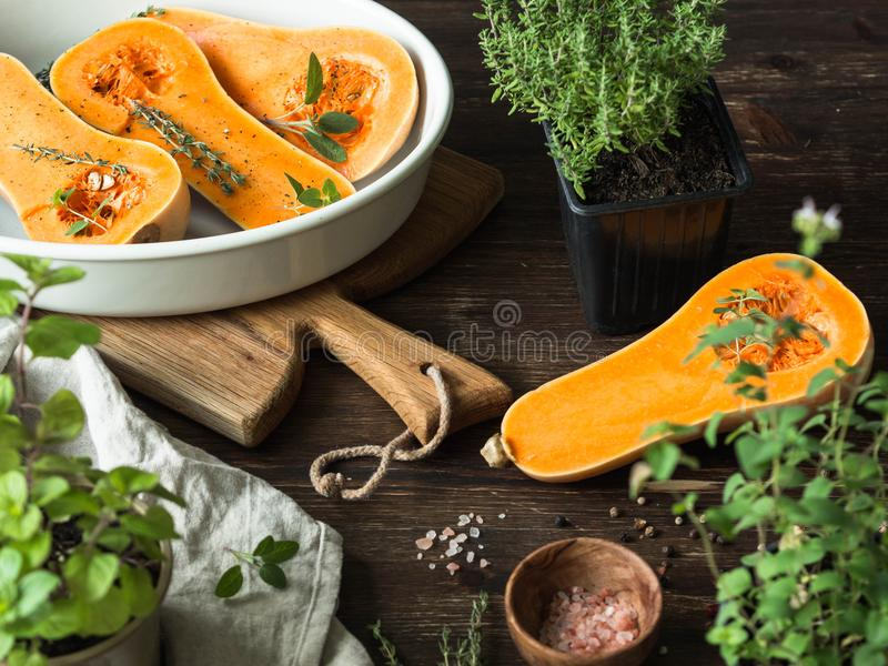 Fresh orange muscat pumpkin, cut in half, ready for baking with spices and herbs on wood board and table. stock photos