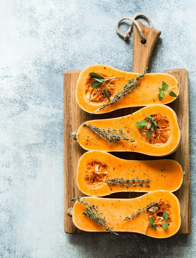 Fresh orange muscat pumpkin, cut in half, ready for baking with spices and herbs on wood board on grey table stock photography