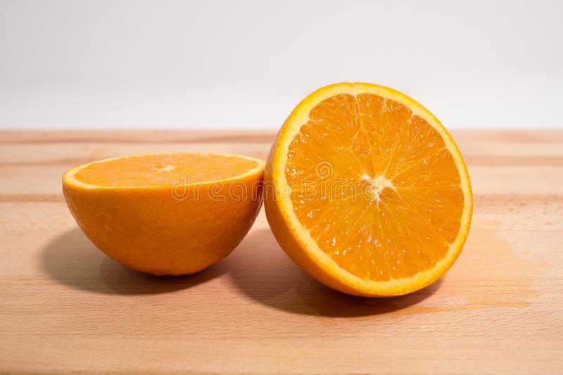 Fresh orange sliced in half on wooden board. Close up side view. stock photos
