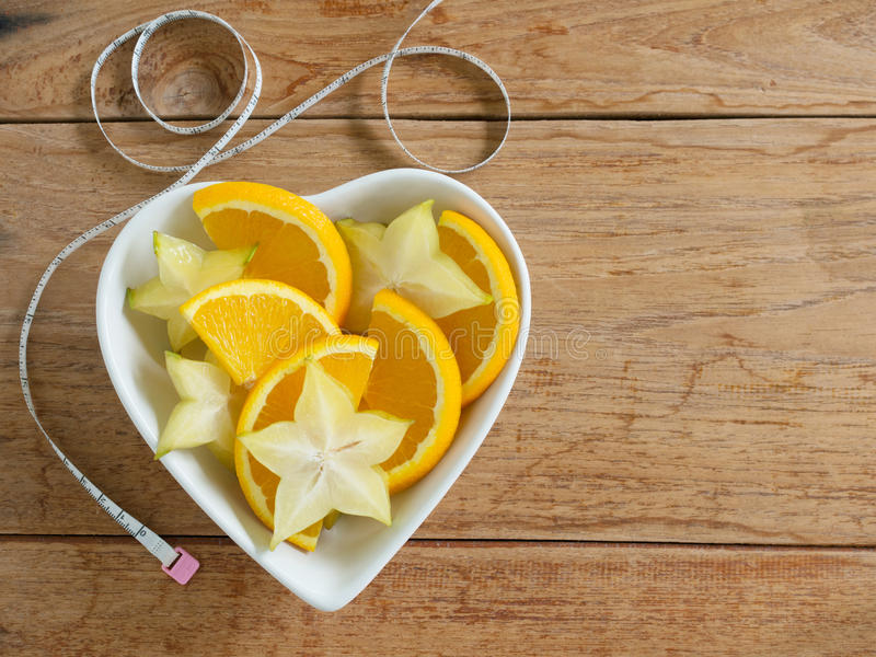 Fresh orange and star fruit slice with measuring tape on table. royalty free stock photo