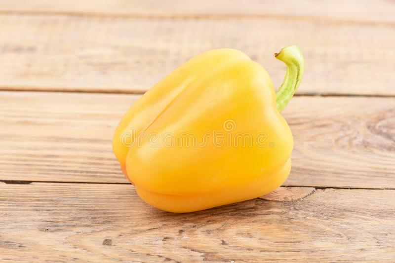 Fresh orange sweet pepper on wooden background royalty free stock photo