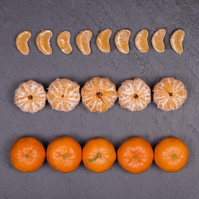 Fresh orange, tangerine fruit, mandarin pattern, top view on a black slate background, close up royalty free stock image
