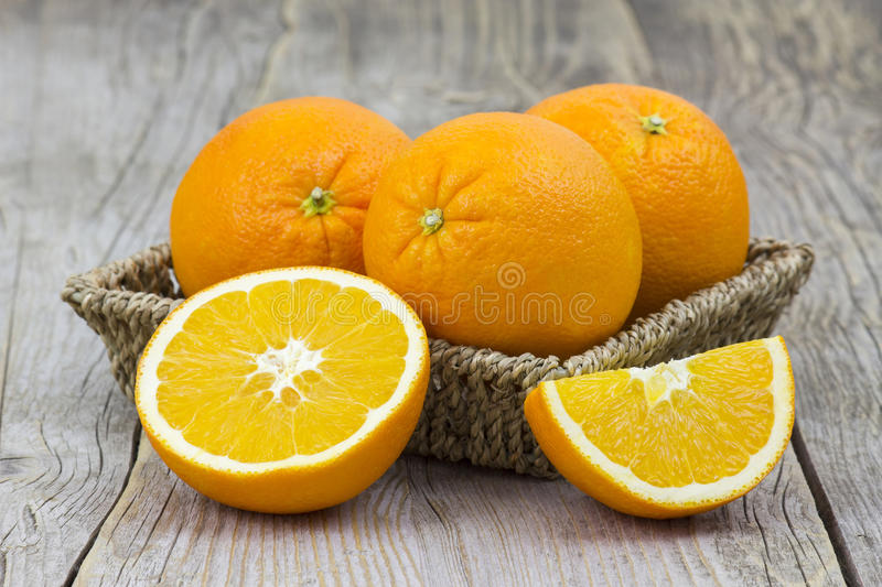 Fresh oranges in a basket. On old wooden background stock images