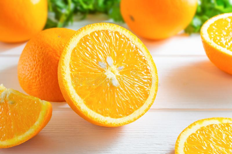 Fresh oranges and green leaves on white wooden table stock photo
