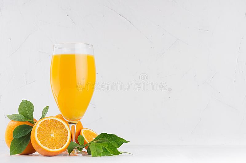 Fresh oranges juice in wineglass with ripe half oranges and green leaf on soft white wood table, copy space. Fresh oranges juice in wineglass with ripe half stock photo