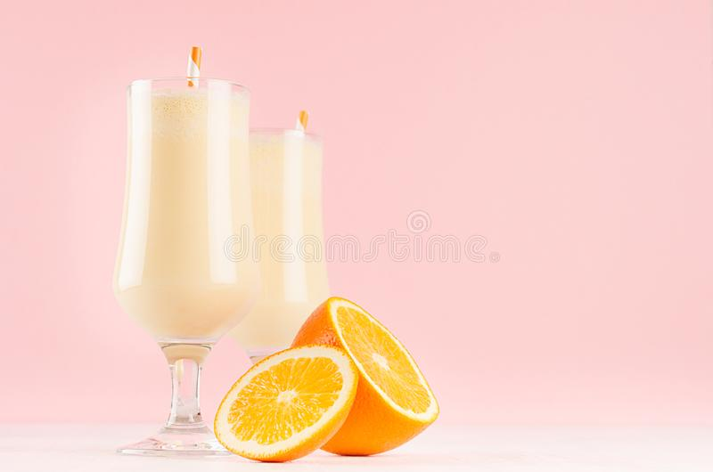 Fresh oranges milkshake in graceful glass with pieces juicy citrus, striped straws on pink background. Fresh oranges milkshake in graceful glass with pieces stock photography