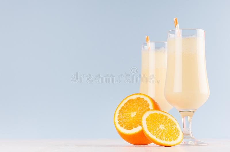 Fresh oranges milkshake with juicy pieces citrus and striped straw in gentle graceful soft light blue interior, copy space. Fresh oranges milkshake with juicy royalty free stock image