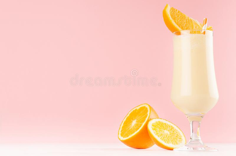 Fresh oranges milkshake with juicy pieces citrus and striped straw in gentle graceful soft pink interior, copy space. Fresh oranges milkshake with juicy pieces royalty free stock images