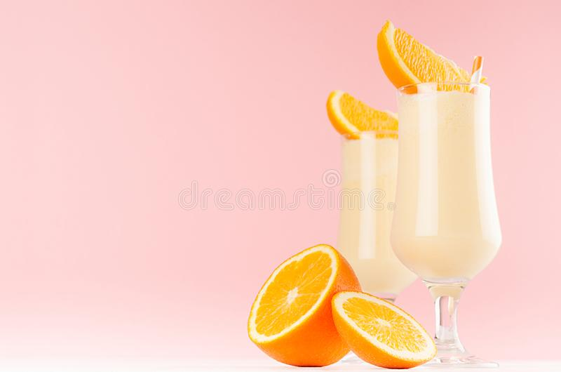 Fresh oranges milkshakes with juicy pieces citrus and striped straws in gentle graceful soft pink interior, copy space. Fresh oranges milkshakes with juicy royalty free stock photography