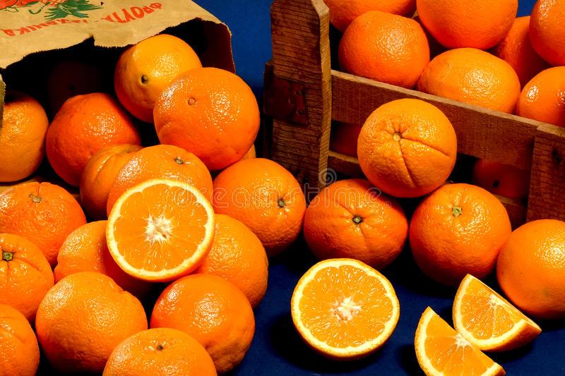 Fresh oranges. In an wooden crate and paper bag. On a blue background stock photography