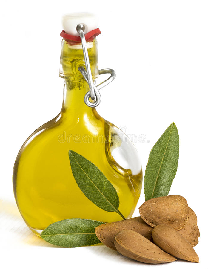 Fresh Organic Almond Oil. In a glass swing top bottle showing picked almonds and green leaves, often used for cooking, therapy, cosmetics, and well being. On a royalty free stock image