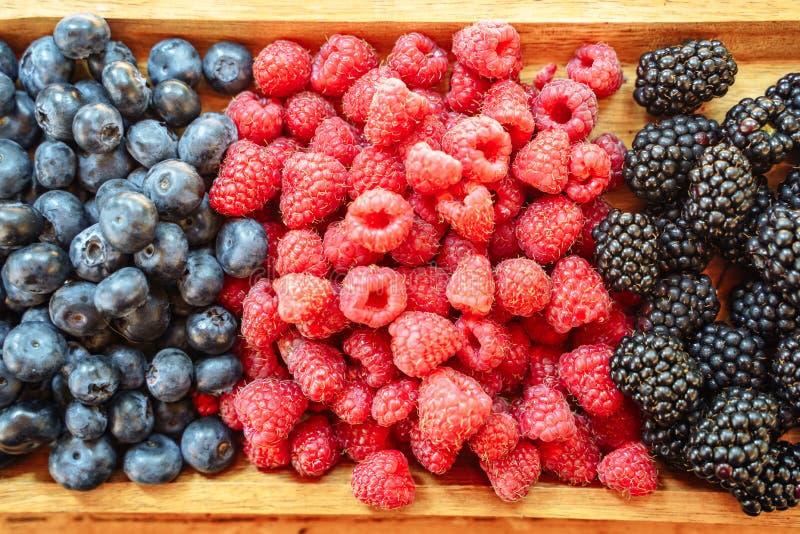 Fresh organic berries - blackberries, raspberries, blueberries on a wooden board stock photography