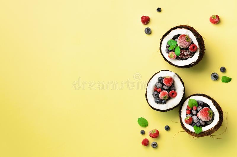 Fresh organic berries, mint leaves inside ripe coconuts on yellow background with copy space. Top View. Pop art design stock image