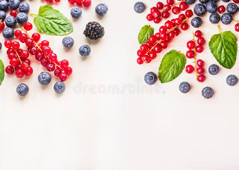 Fresh organic berries with mint leaves and water drops on white wooden background, top view. Place for text stock images