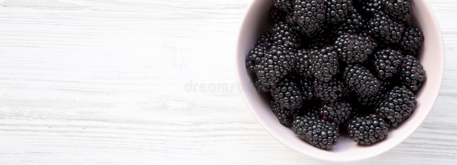 Fresh organic blackberries in pink bowl on a white wooden surface. Close-up. Copy space stock image