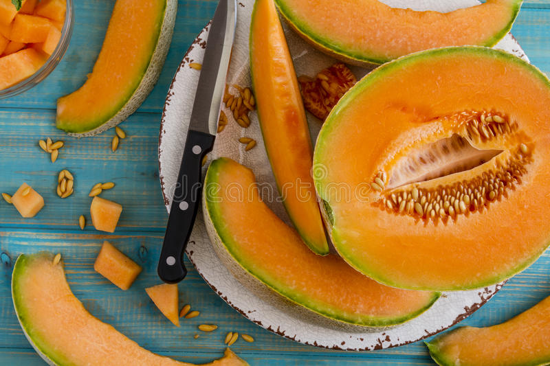 Fresh organic cantaloupe melon. Cut open cantaloupe melon half and slices sitting on white rustic plate on bright blue wooden tabletop with knife royalty free stock images