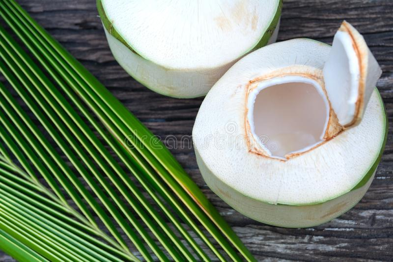 Fresh organic coconut water with coconut leaves on wooden table.  royalty free stock photo