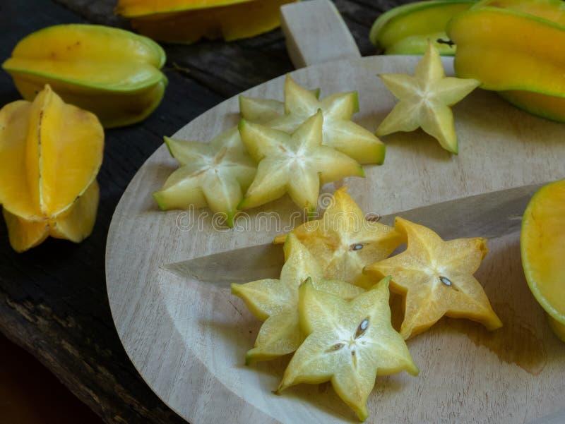 Fresh organic cut star fruit on wooden chopping board stock photos