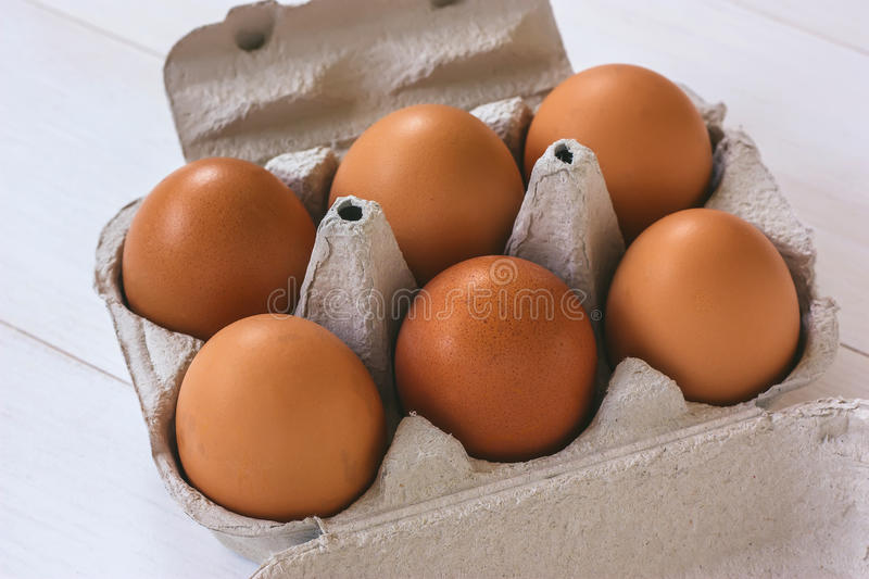 Fresh organic eggs in a carton. On a white wooden table royalty free stock photo