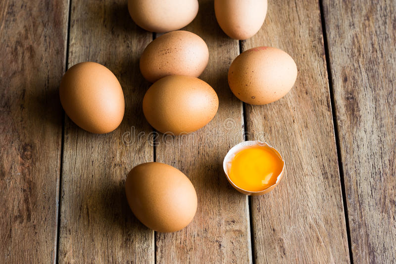 Fresh organic eggs scattered on wood kitchen table, cracked shell with open yolk, soft daylight, baking, Easter concept. Top view stock photos