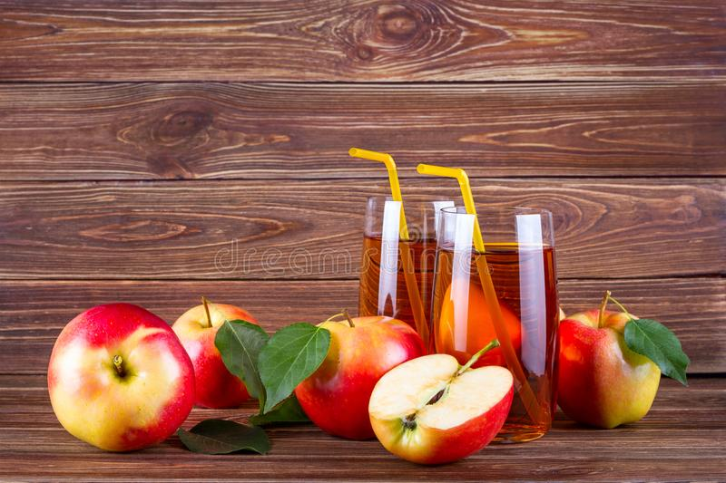 Fresh organic farm apple juice in glass with raw whole and sliced red apples royalty free stock photos