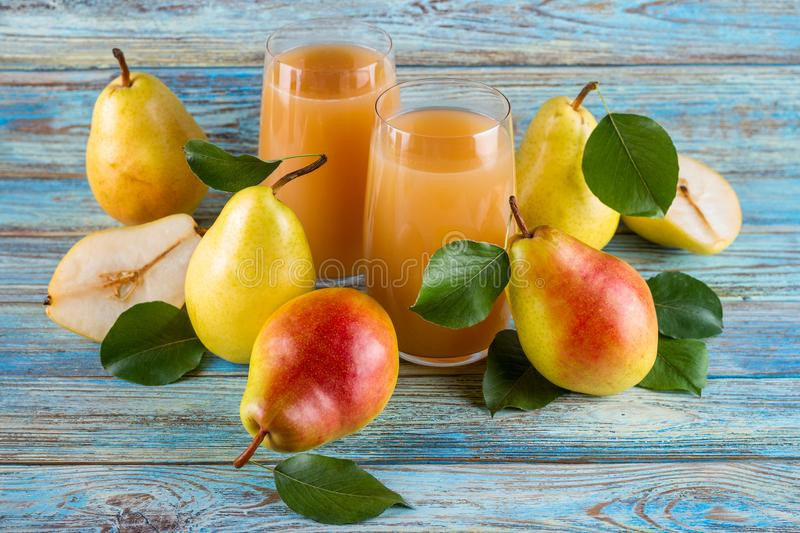 Fresh organic farm pear juice in glass with raw whole and sliced pears royalty free stock images