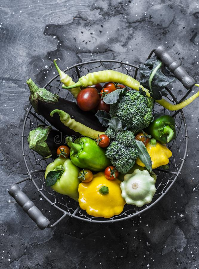 Fresh organic farm vegetables - broccoli, eggplant, pepper, tomatoes, squash in a basket on a dark background, top view. Healthy stock image