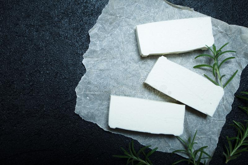 Fresh organic feta cheese with rosemary on white paper, top view. Space for text royalty free stock photography