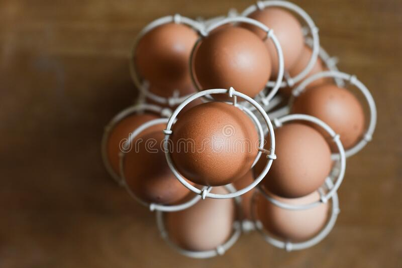 Fresh organic free range eggs in a rack on a wooden background stock photo