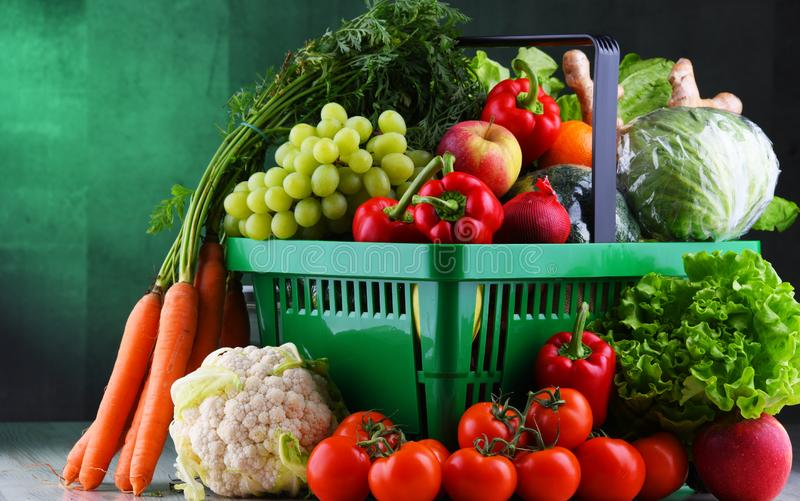 Fresh organic fruits and vegetables in plastic shopping basket royalty free stock photos