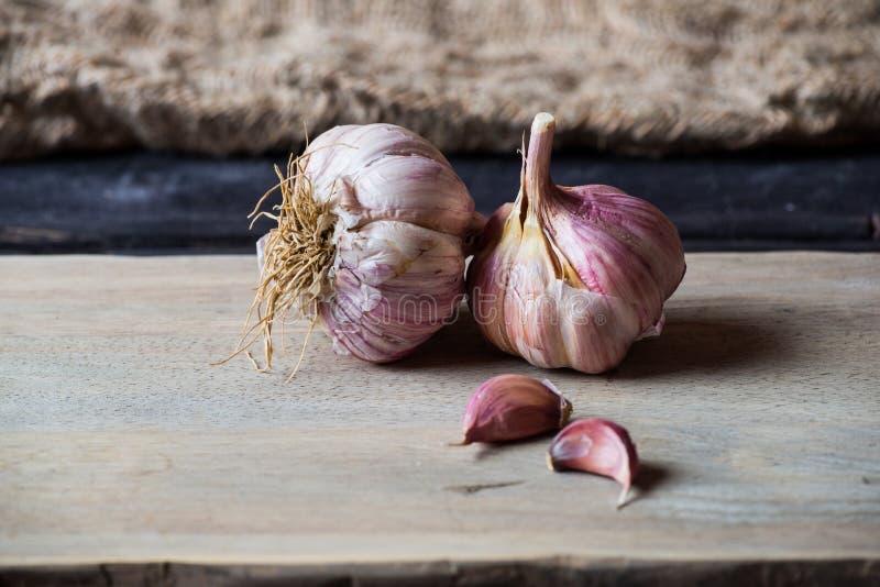 Fresh organic garlic. On dark wooden background stock photography
