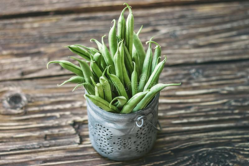 Fresh organic green beans in a metallic bowl on a rustic table royalty free stock images
