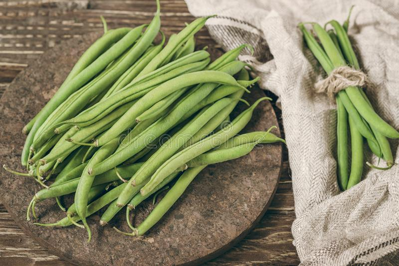 Fresh organic green beans on a rustic wooden table top view. royalty free stock photo
