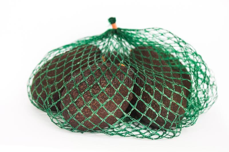 Fresh organic hass avocados in a green string bag on a white background isolated, healthy food concept, copy space stock photo