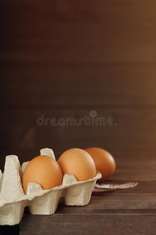 Rustic Easter background. Fresh organic hen eggs in tray on wooden background. Rustic holiday background. Easter concept. Copy space stock photography