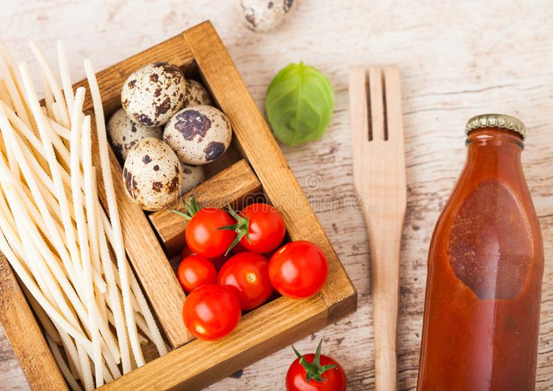 Fresh organic hommemade spaghetti pasta with quail eggs and fresh tomatoes with bottle of tomato sauce and wooden spatula and basi. L leaf on wooden board royalty free stock images