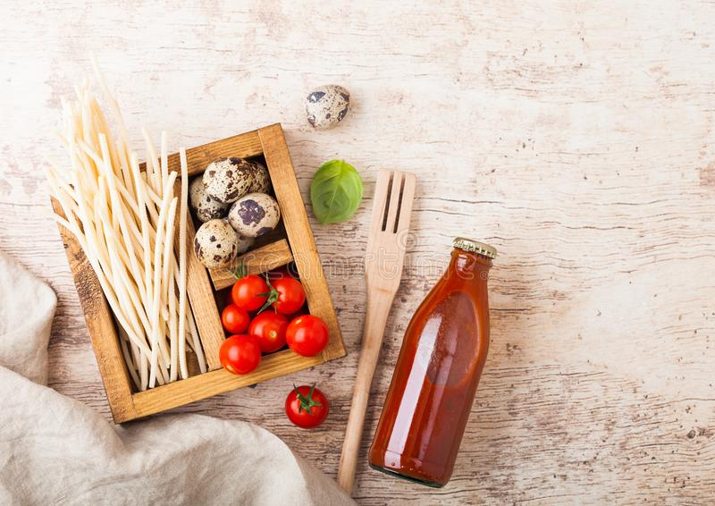 Fresh organic hommemade spaghetti pasta with quail eggs and fresh tomatoes with bottle of tomato sauce and wooden spatula and. Basil leaf on wooden board stock images