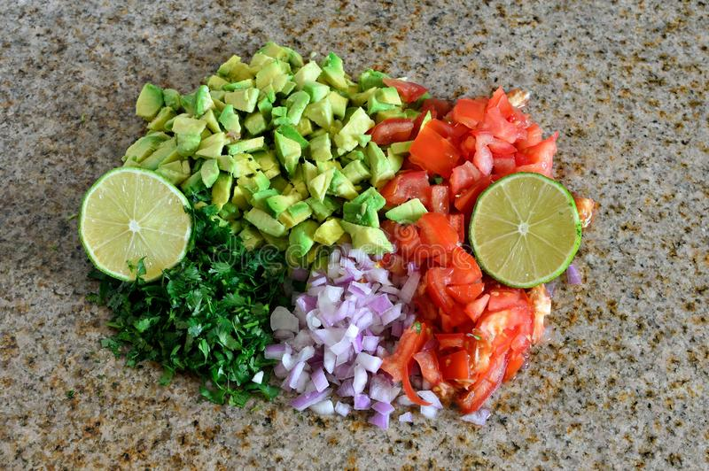 Fresh organic ingredients chopped for salsa, avocado, tomato, lime. on granite kitchen counter. Fruit, Red, Green, Dark stock photos