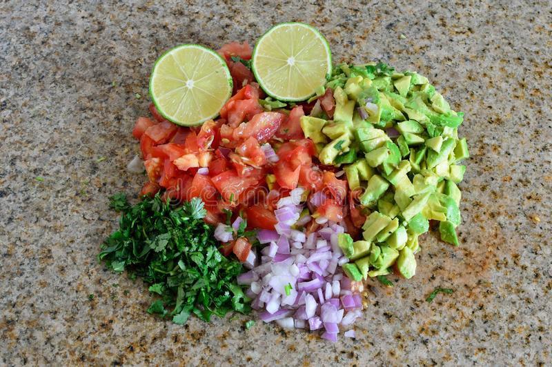 Organic ingredients chopped for salsa, avocado, tomato, lime. Fresh organic ingredients chopped for salsa, avocado, tomato, lime. on granite kitchen counter royalty free stock images