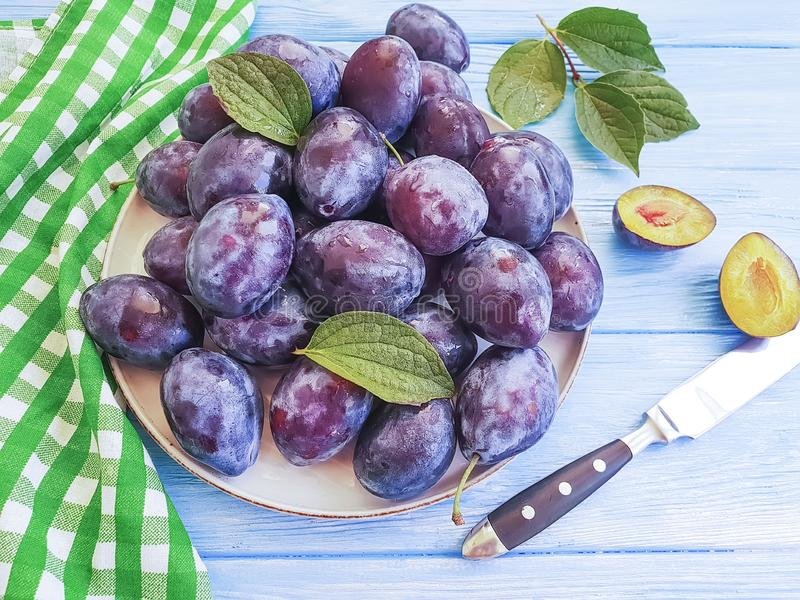 Fresh organic juicy dessert plum vitamin natural autumn delicious on a plate table , blue wooden background, towel royalty free stock image