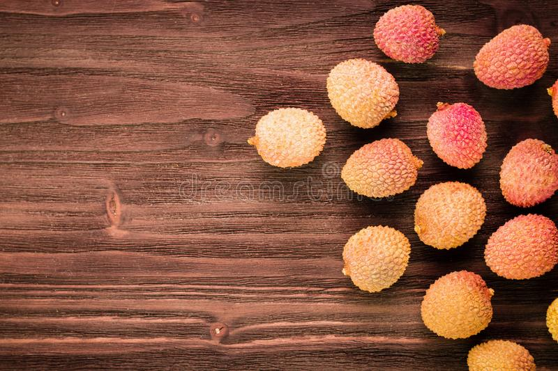 Fresh organic lychee fruits on brown wooden background royalty free stock photos